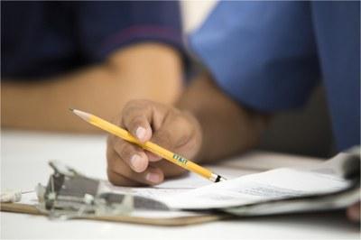 Studierender hält Bleistift mit Aufschrift